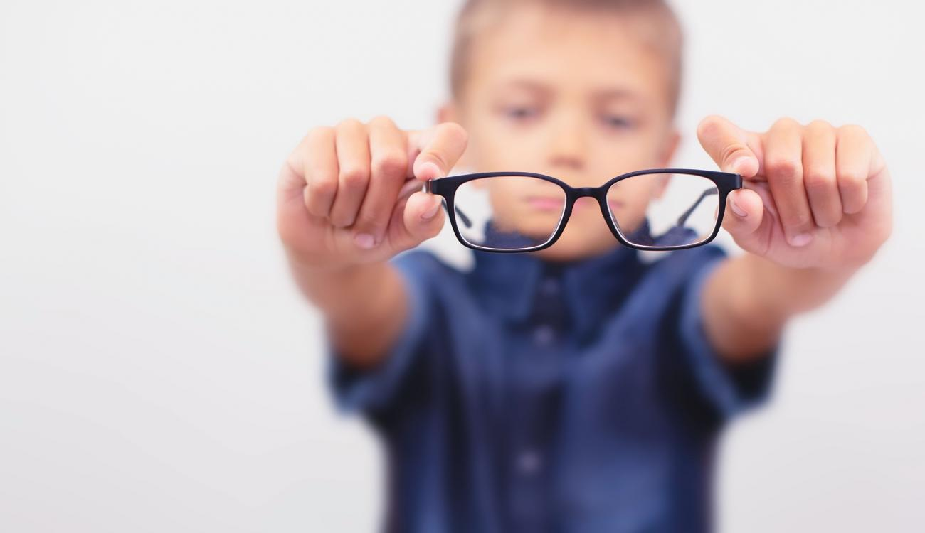 A child holding a pair of glasses.  The only part of the image in focus is what can be seen through the glasses.